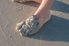 Person, die im Sand auf einem Strand spielt Lizenzfreies Stockbild