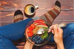Person, die im Schneidersitz auf Bretterboden frühstückt Lizenzfreies Stockfoto