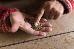 Person, die kleine Veränderung in der Palme der Hand zählt Lizenzfreies Stockfoto