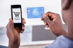 Person, die Kreditkarte und Handy hält stockfotos