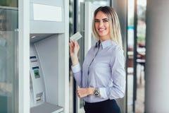 Person, die Kreditkarte zum R?ckzug des Geldes von ATM-Maschine verwendet lizenzfreies stockbild