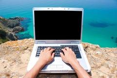 Person, die Laptop durch das Meer verwendet Lizenzfreies Stockbild