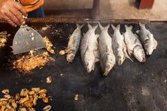 Person, die Miesmuscheln und Fische auf einem Grill kocht Lizenzfreie Stockfotos