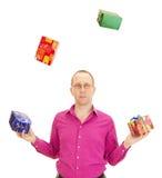 Person, die mit einigen bunten Geschenken jongliert Stockfotografie