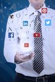 Person, die Mobiltelefon mit Ikonen des Sozialen Netzes hält Stockfotografie