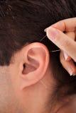 Person, die Nadel nahe Ohr hält Stockfoto
