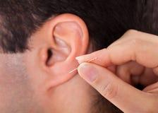 Person, die Nadel nahe Ohr hält Stockbilder