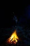 Person, die nahe von einem Feuer sitzt Lizenzfreies Stockfoto