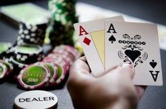 Person, die Poker spielt und Karten betrachtet lizenzfreie stockbilder