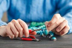 Person, die Schmuck unter Verwendung des Drahtes, Ketten und Perlen und andere Materialien mit Handwerkswerkzeugen macht lizenzfreies stockfoto