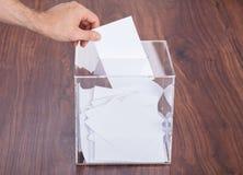 Person, die Stimmzettel in Kasten einsetzt Lizenzfreies Stockfoto