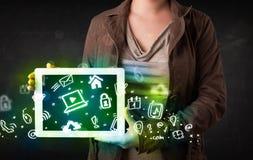 Person, die Tablette mit grünen Medienikonen hält Lizenzfreie Stockfotografie