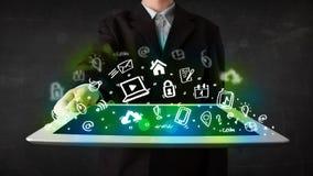 Person, die Tablette mit grünen Medienikonen und -symbolen hält Stockbild