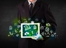 Person, die Tablette mit grünen Medienikonen und -symbolen hält Stockfotografie