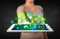 Person, die Tablette mit grünen Medienikonen und -symbolen hält Stockfoto