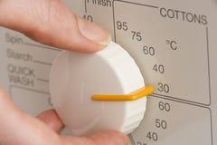 Person, die Waschmaschine-Vorwahlknopf auf kalte Wäsche justiert Stockbilder