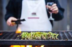 Person, die Weinglas hält und Spargel grillt Stockfoto
