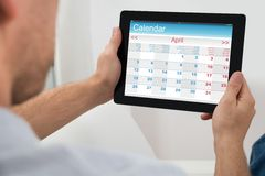 Person With Digital Tablet Showing-Kalender Stock Foto