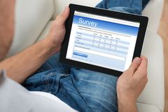Person With Digital Tablet Showing Survey Form Royalty Free Stock Images