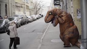 Person in dinosaur costume dancing at city street alley. Sidewalk. Cold sunny spring or autumn day, lots of parked cars. Slow motion stock footage