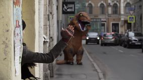 Person in dinosaur costume waves arm at girl at city street alley. Cold sunny spring or autumn day, lots of parked cars. Slow motion stock video footage