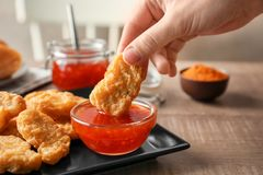 Person dipping chicken nugget in chili. Sauce indoors stock images