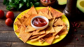 Person dipping corn tortilla chip into tomato sauce. Tex mex or traditional Mexican snack food stock footage