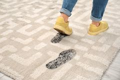 Person in dirty shoes leaving muddy footprints. On carpet stock photography