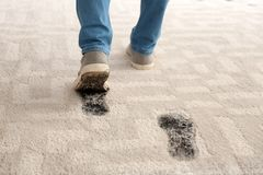 Person in dirty shoes leaving muddy footprints. On carpet stock image