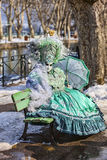 Person Disguised in a Green Costume. Annecy, France- February 24, 2013:Unidentified person disguised in a beautiful green costume sits on a bench in Annecy Royalty Free Stock Images