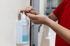 Person dispensing disinfectant sanitizer liquid onto hand in hos