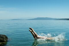 Person Diving on Body of Water during Daytime Stock Photo