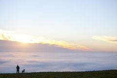 Person and dog on hill viewing sunrise and fog covered landscape Royalty Free Stock Image
