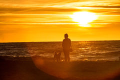 A person with a dog at sunset. A person with a dog standing on the background of the sunset over the sea Royalty Free Stock Images