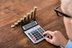 Person Doing Calculation On Saving. Person Hand Doing Calculation On Stacked Coin And Piggybank At Wooden Desk. Income Tax Concept stock image