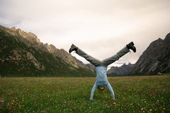 Person doing a handstand on mountain meadow Stock Photography
