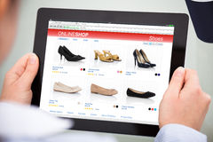 Person Doing Online Shopping On Digital Tablet. Close-up Of Person Purchasing Footwear While Doing Online Shopping On Digital Tablet Stock Photography