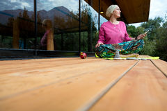 Person doing Yoga Exercise on wooden Terrace of rural Cabin Royalty Free Stock Photo