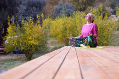 Person doing Yoga Exercise on wooden Terrace of rural Cabin Stock Photos