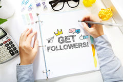 Person drawing Get More Followers concept on white paper Stock Photo