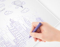 A person drawing sketch of a city with balloons and clouds on a Royalty Free Stock Images