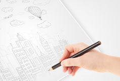 A person drawing sketch of a city with balloons and clouds on a Royalty Free Stock Photo