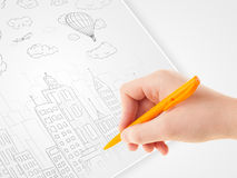 A person drawing sketch of a city with balloons and clouds on a Royalty Free Stock Photos