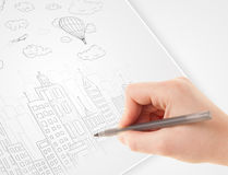 A person drawing sketch of a city with balloons and clouds on a Stock Image