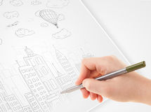 A person drawing sketch of a city with balloons and clouds on a Royalty Free Stock Image