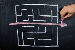 Person Drawing Straight Red Line Over Maze. Close-up Of Person Drawing Straight Red Line Over Maze On Blackboard stock images
