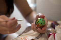 A person draws a brush on an Easter egg with different colors stock image