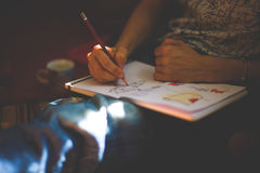 A person draws with a pencil in a notebook. Stock Image