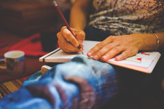 A person draws with a pencil in a notebook. Royalty Free Stock Images