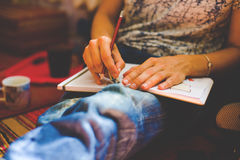 A person draws with a pencil in a notebook. Stock Photos